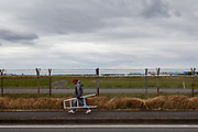 A military aircraft enthusiast carries his camera and step ladder   away along the fence of Naval Air Facility, Atsugi airbase just after three  F18 fighter jets had taken off. Yamato, Kanagawa, japan. Monday April 29th 2019. The F18 of the Royal Aces squadron is a rare visitor to this US and Japan Self Defence Force base in Kanagawa. Once stationed there the jets, which were the cause of lawsuits related to noise levels by local residents, have been moved to Iwakuni airbase. Many aircraft enthusiasts still turn put to watch and photograph them when they visit however..