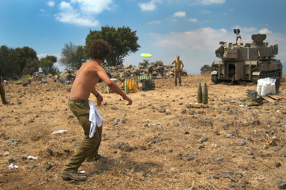 IDF artillery soldiers playing Frisbee between hectic firing towards Hizbullah targets at southern Lebanon. 2nd Lebanon War. Israel, August 2006.
