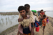 Sunday 12th November, 2017. Mohammed Hossain, 23, from Yanshong, Buthedaung in Myanmar carrying his father Abdu Shakkur, 60. <br /> <br /> After 16 - 20 days waiting on the Myanmar border, Rohingya refugees cross the Naf River into Bangladesh using eight make-shift rafts. <br /> <br /> Often described as the &quot;world's most persecuted minority&quot;, the Rohingya are a Muslim ethnic group from the Rakhine State in Myanmar. In October 2016, a military crackdown in the wake of a deadly attack on an army post sent hundreds of thousands of Rohingya fleeing to neighbouring Bangladesh. Photograph by David Dare Parker