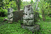 Pauto and Mani Tikis, in red keetu or volcanic tuff, carved into a small paepae or platform of a tomb, with Pauto (left), 80cm tall, with crowned and patterned head, tattooed mouth, pierced right armpit, hands on either side of the belly, and male genitalia, and Mani (right), 77cm tall, with crowned head, tattooed face, hand resting under the chin and broken male genitalia, on the tomb of the daughter of the chief, at Tohua Pehekua, a small cemetery with 4 tombs of chief Te Hau Moea and his family, who died in the early 20th century, near the Iipona archaeological site, near the village of Puamau, on the island of Hiva Oa, in the Marquesas Islands, French Polynesia. Tiki sculptures are usually carved in wood or stone and represent Ti'i, a half-human half-god ancestor who is believed to be the first man. Tiki often have a huge head, symbolising power, and big eyes symbolising knowledge. Tiki are respected and are often placed outside houses or tombs as protective statues. Picture by Manuel Cohen
