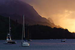 Anchored sailboats in Hanalei Bay against a backdrop of the north shore cliffs of the Na Pali coast at sunset on the island of Kauai near the north shore town of Hanalei in Hawaii.