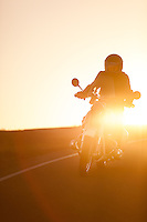 Brent Greenwood (MR) riding his 1960s BMW R60US motorcycle (PR) on a coastal road in Sonoma County California at sunset.