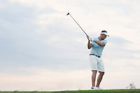 Mid-adult man playing golf against sky