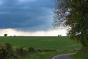 Dark stormy leaden sky with rain cloud forecasts inclement bad weather in Swinbrook in The Cotswolds, Oxfordshire, UK