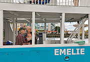 A middle aged couple enjoy the siights aboard the tour boat Emelie, Stockholm, Sweden. The amusement park Tivoli Gröna Lund can be seen in the background.