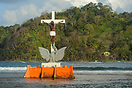 """Isla Grande is an exciting and popular place in Panama that people simply know as """"La Isla"""" (The Island). The island is inside the Portobelo National park, just 5 minutos by motor boat from the small town of La Guaira on the main land that makes its living out fishing and tourism.Pictured: sculpture of a black christ over the ocean surface."""
