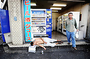 "A homeless man lies outside a booth containing several  automatic vending machines selling alcoholic  drinks the Kamagasaki district of Osaka, Japan. Alcoholism afflicts a sizable portion of the city's homeless, with drinks machines such as those shown in this picture selling almost entirely low-priced beers and ""sake"", a wine-like beverage fermented from rice.."