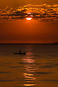 A rowboat in Charleston harbor during sunrise along the Battery in historic Charleston, SC.