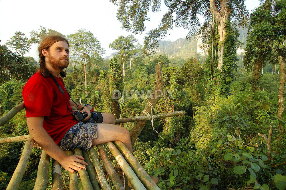 GIS specialist Shane Fryer takes in a 360 degree view from the forest canopy platform near Lake Tebo.