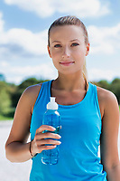 Portrait of young attractive woman drinking energy drink in park