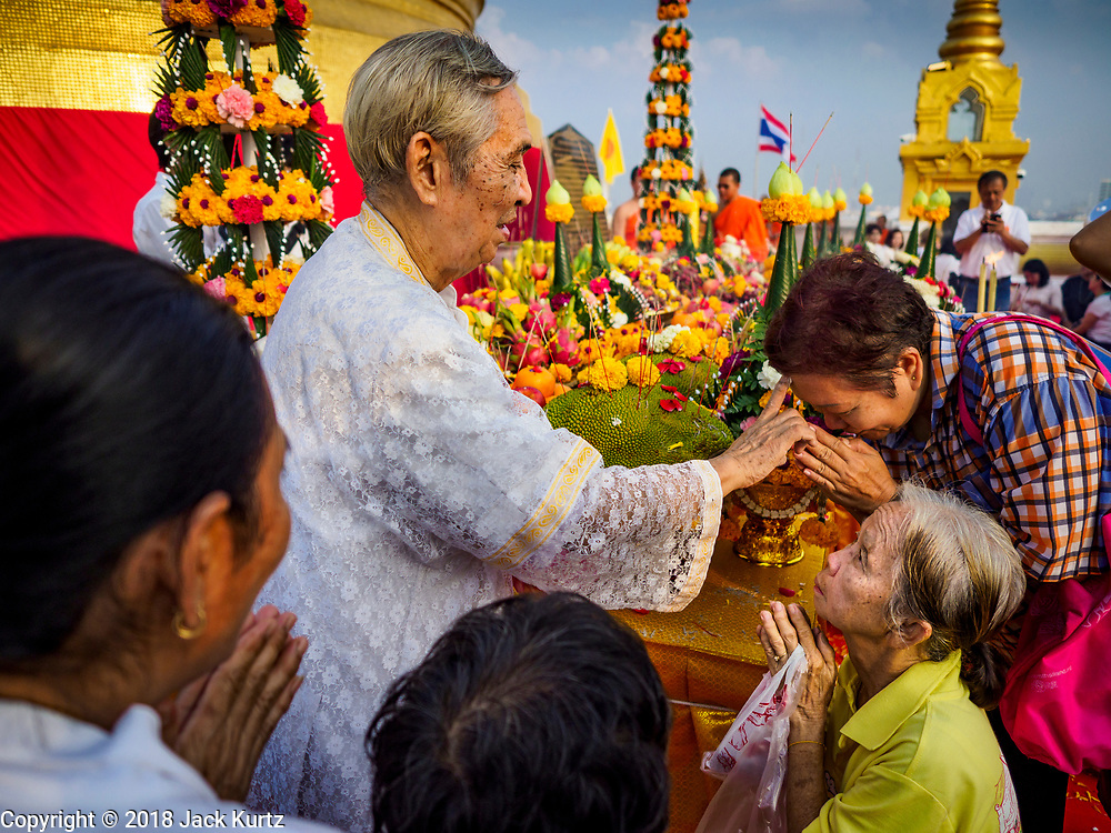 15 NOVEMBER 2018 - BANGKOK, THAILAND: A Brahmin priest blesses people during the red cloth ceremony at the top of Wat Saket, also called the Golden Mount. Wat Saket is on a man-made hill in the historic section of Bangkok. The temple has golden spire that is 260 feet high, which was the highest point in Bangkok for more than 100 years. The temple construction began in the 1800s during the reign of King Rama III and was completed in the reign of King Rama IV. A  red cloth (reminiscent of a monk's robe) is placed around the chedi at the top of  Golden Mount during the weeks leading up to the Thai holy day of Loy Krathong, which is November 22 this year.     PHOTO BY JACK KURTZ