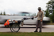 """DACULA, GA – JUNE 6, 2014: Karl Bushby rests amid passing cars on Highway 124. Bushy walks about 20 miles a day, and has admitted that his quest to get permission to travel through Russia is a long shot. """"If I skip Russia and just start walking through China, I've failed.""""<br /> <br /> Karl Bushby is trying to complete the longest walk in history. Unless the Russians stop him. As a 45 year-old Brit, Bushby been traveling around the world on foot since 1998. In the most recent leg of his journey, Bushby is walking to Washington, D.C. to petition the Russian Embassy to lift a visa ban that prohibited him from continuing his hike through Russia."""