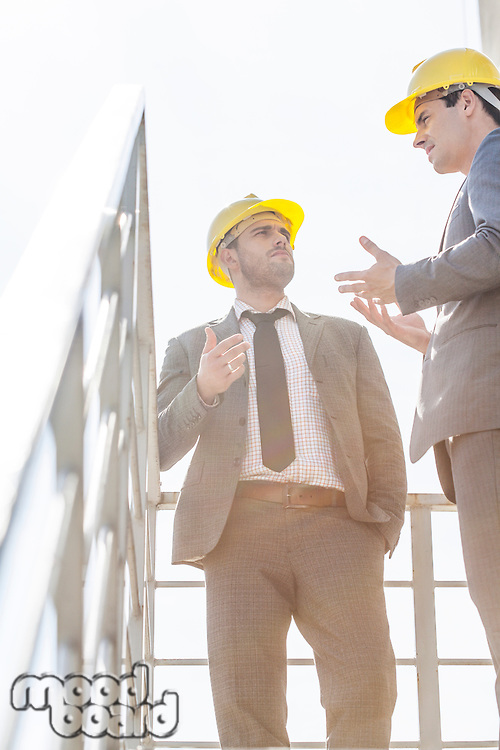 Low angle view of young male businessmen in hard hats having discussion on stairway against clear sky