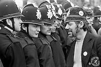 Striking miner wearing a joke police helmet talking to Police at Orgreave. 6 June 1984