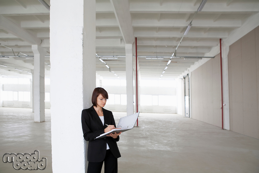 Business woman leans against pillar with file in empty warehouse