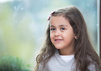 Portrait of cute little girl against glass window at home