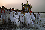 A mikoshi and supporters at sunrise during the Hamaorisai matsuri on Southern Beach in Chigasaki, Kanagawa, Japan. Monday July 18th  2005. The festivals marks the celebration of Marine Day in July. Over thirty Mikoshi or portable shrines are carried through the night from surrounding shrines to arrive on the beach for sunrise. They are then carried into the surf to purify them.