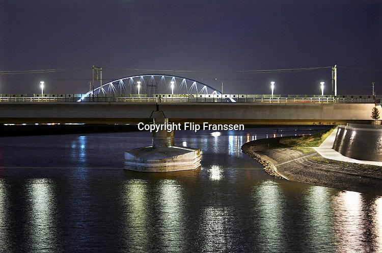 Nederland, Nijmegen, 14-8-2016 Sfeerbeeld bij maanlicht van het Rivierpark en het eiland Veur-Lent, lentereiland . Resultaat van het project Ruimte voor de Rivier. De versterkte pijlers van de spoorbrug. Op de achtergrond de nieuwe brug de OversteekFoto: Flip Franssen