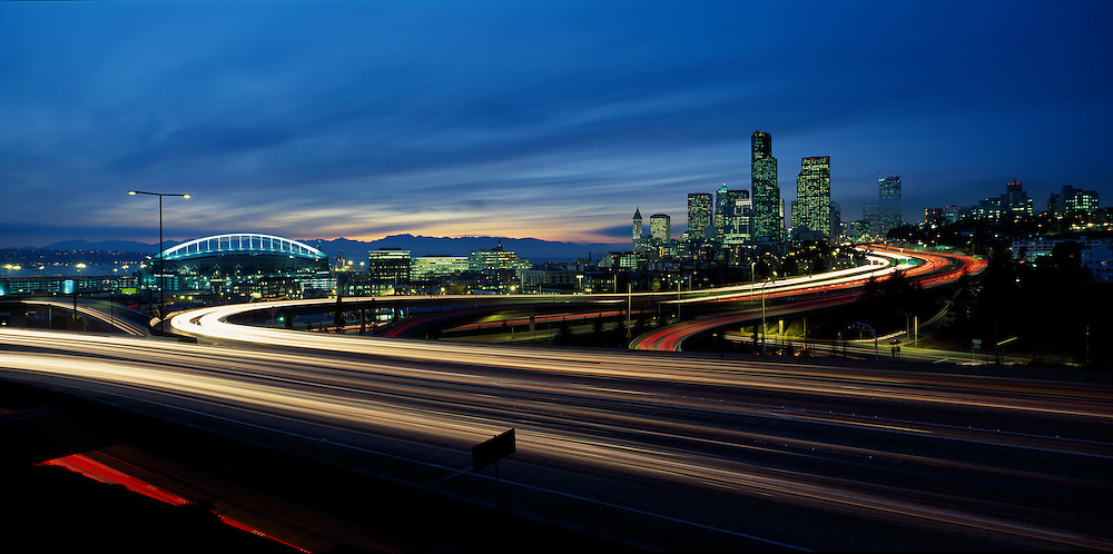 USA, Washington, Seattle, Downtown skyline and Seahawks Stadium with evening rush hour traffic on autumn evening