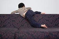 Boy (5-6) climbing over sofa