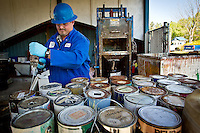 Marc Branscome punctures drainage holes into the top of discarded paint cans that were dropped off by Kootenai County residents for disposal at the household hazardous waste collection site in Coeur d'Alene.