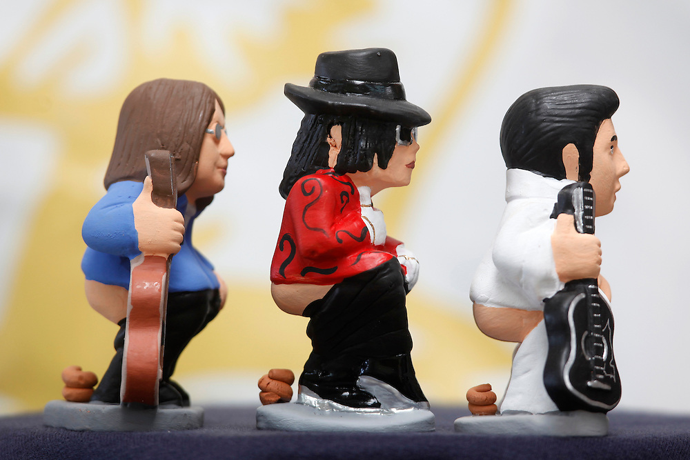 "November 10,  2010. A company in Torroella de Montgrí (Girona, Spain) called ""Caganer.com"", which specializes in the production of ""caganers"", unveiled today its new figurine for Christmas, Michael Jackson, Josn Lennon or prince Charles. .A ""Caganer"" is a small figure from Catalonia, usually made of fired clay, which depicts as squatting person in the act defecating..""Caganer"" is Catalan for pooper. It forms part of one of the typical figures of the manger or ""Nativity"" scene together with Mary, Joseph and the baby Jesus but hidden in a corner. It is a humorous figure, originally portraying a peasant wearing a ""barretina"" (a red stocking hat), and seems to date from the 18th century when it was believed that the figure's deposits would fertilize the earth to bring a prosperous year. With the course of time, the original personage of this pooping figure was substituted with personalities from the political and sports worlds and other famous personalities..From left to right singers John Lennon, Michael Jackson and Elvis Presley."