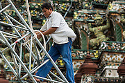 "23 SEPTEMBER 2013 - BANGKOK, THAILAND: Workers put up scaffolding around a chedi at Wat Arun in Bangkok. The full name of the temple is Wat Arunratchawararam Ratchaworamahavihara. The outstanding feature of Wat Arun is its central prang (Khmer-style tower). The world-famous stupa, known locally as Phra Prang Wat Arun, will be closed for three years to undergo repairs and renovation along with other structures in the temple compound. This will be the biggest repair and renovation work on the stupa in the last 14 years. In the past, even while large-scale work was being done, the stupa used to remain open to tourists. It may be named ""Temple of the Dawn"" because the first light of morning reflects off the surface of the temple with a pearly iridescence. The height is reported by different sources as between 66,80 meters and 86 meters. The corners are marked by 4 smaller satellite prangs. The temple was built in the days of Thailand's ancient capital of Ayutthaya and originally known as Wat Makok (The Olive Temple). King Rama IV gave the temple the present name Wat Arunratchawararam. Wat Arun officially ordained its first westerner, an American, in 2005. The central prang symbolizes Mount Meru of the Indian cosmology. The temple's distinctive silhouette is the logo of the Tourism Authority of Thailand.           PHOTO BY JACK KURTZ"