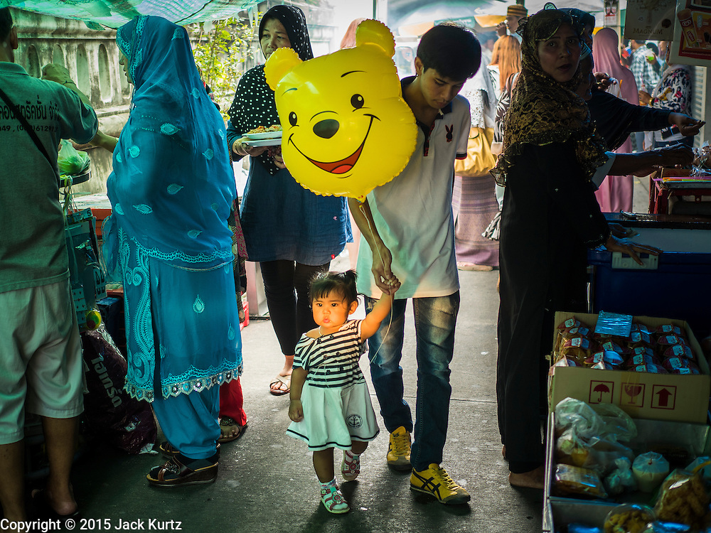 17 JULY 2015 - BANGKOK, THAILAND:     People walk through a street food market in front of Ton Son Mosque in Bangkok after Eid services. Eid al-Fitr is also called Feast of Breaking the Fast, the Sugar Feast, Bayram (Bajram), the Sweet Festival or Hari Raya Puasa and the Lesser Eid. It is an important Muslim religious holiday that marks the end of Ramadan, the Islamic holy month of fasting. Muslims are not allowed to fast on Eid. The holiday celebrates the conclusion of the 29 or 30 days of dawn-to-sunset fasting Muslims do during the month of Ramadan. It's common to give children small gifts and toys, like helium balloons, for Eid. Islam is the second largest religion in Thailand. Government sources say about 5% of Thais are Muslim, many in the Muslim community say the number is closer to 10%.          PHOTO BY JACK KURTZ