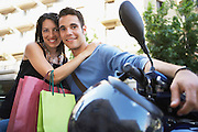 Young couple on motor scooter with shopping bags portrait