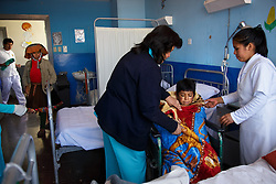 Nurses at Hospital Regional Cusco prepare to take Fernando Quispe Melo, 14, downstairs for an X-ray. After the teen injured his leg, Fernando's mother carried him three hours to the nearest clinic, where an ambulance ferried him to the hospital. By then, he had a staph infection so severe, doctors weren't sure they could save him. But after an operation and several weeks of antibiotics, Fernando was improving. Meanwhile, his mother, Dionisia Melo Mesa, at rear, refused to leave his side.