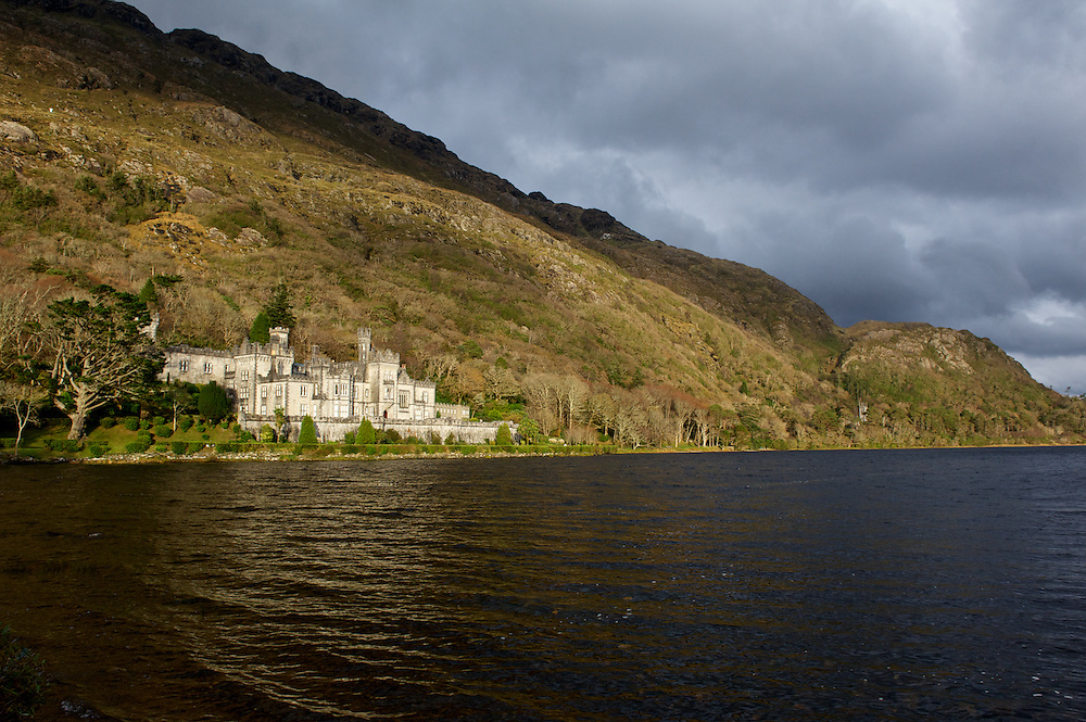 Kylemore Abbey viewed over the waters of Lake Pollacappul in County Galway, Ireland as the sun breaks through an autumn sky.