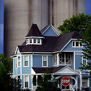 Grain elevators tower over an 1886 Victorian Queen Anne home in Prairie City, Iowa.   Built by Levi Springer, who owned the local lumber yard, the home has been restored by it's current owners Dennis and Jean Cook.