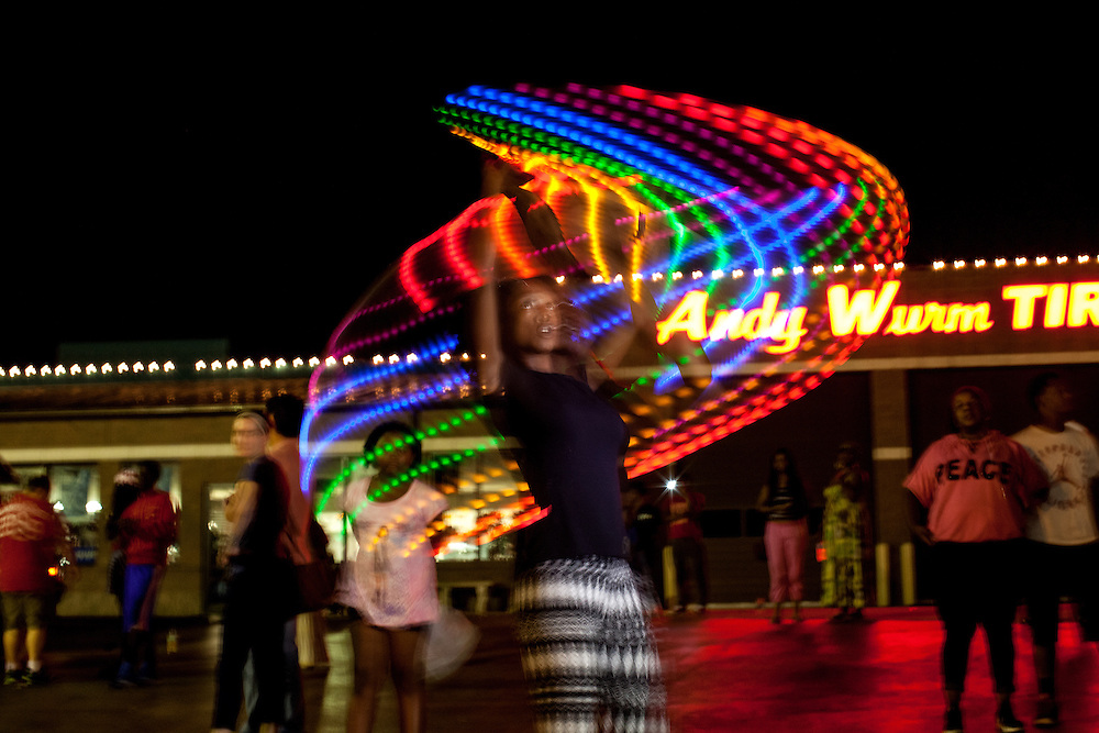 "A protestor ""dances"" and twirls with a multi-colored light stick. Across from the Ferguson police station, a carnival-type atmosphere begins to take shape as more demonstrators take to the streets after the shooting death of Michael Brown Jr."