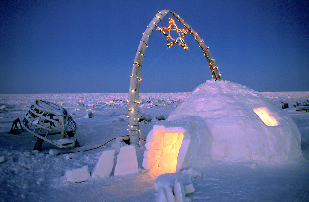 Barrow, Alaska, Christmas lights adorn an igloo and whale bones on the beach. The frame of a traditional umiak stands nearby.