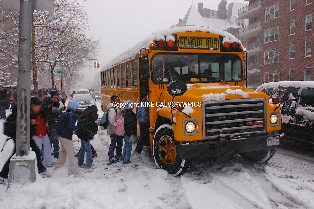 Kids going to school and entering a yellow bus. Snow blizzard in New York City