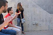 Monica Nezzer looks up as she waits with coworkers Alexander Gordon (middle) and Patrick Arite for students from a local charter school on Thursday June 2, 2016. Monica Nezzer and Patrick Arite are both students at the University of New Mexico and are working 15-30 hours per week giving campus tours in order to help put themselves through college. (Steven St. John for NPR)