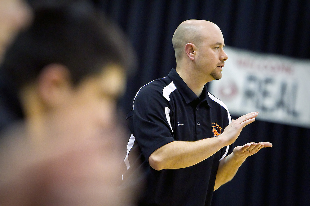 JEROME A. POLLOS/Press..Post Falls High's coach Mike McLean cheers on his team as they take the floor for the second half of the Trojan's tournament opener against Vallivue High at the state 5A championships Thursday.