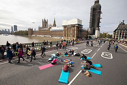 © Licensed to London News Pictures. 07/10/2019. London, UK. Extinction Rebellion protesters take part in a yoga session on Westminster Bridge . Photo credit: George Cracknell Wright/LNP