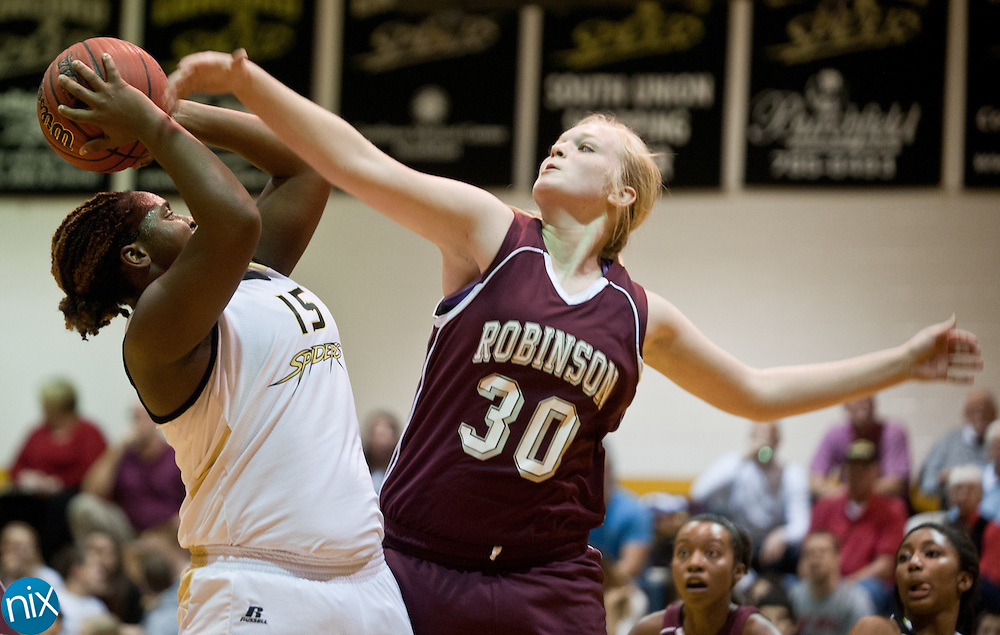 Concord's Alleson Briggs looks to shoot against Jay M. Robinson's Rachel Cook Friday night at Concord High School. The Spiders won the game 71-68.  (Photo by James Nix)