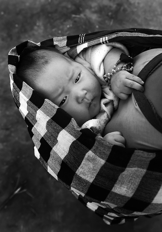 A Hmong baby is very comfortable on a boys back in Luang Namtha, Laos.