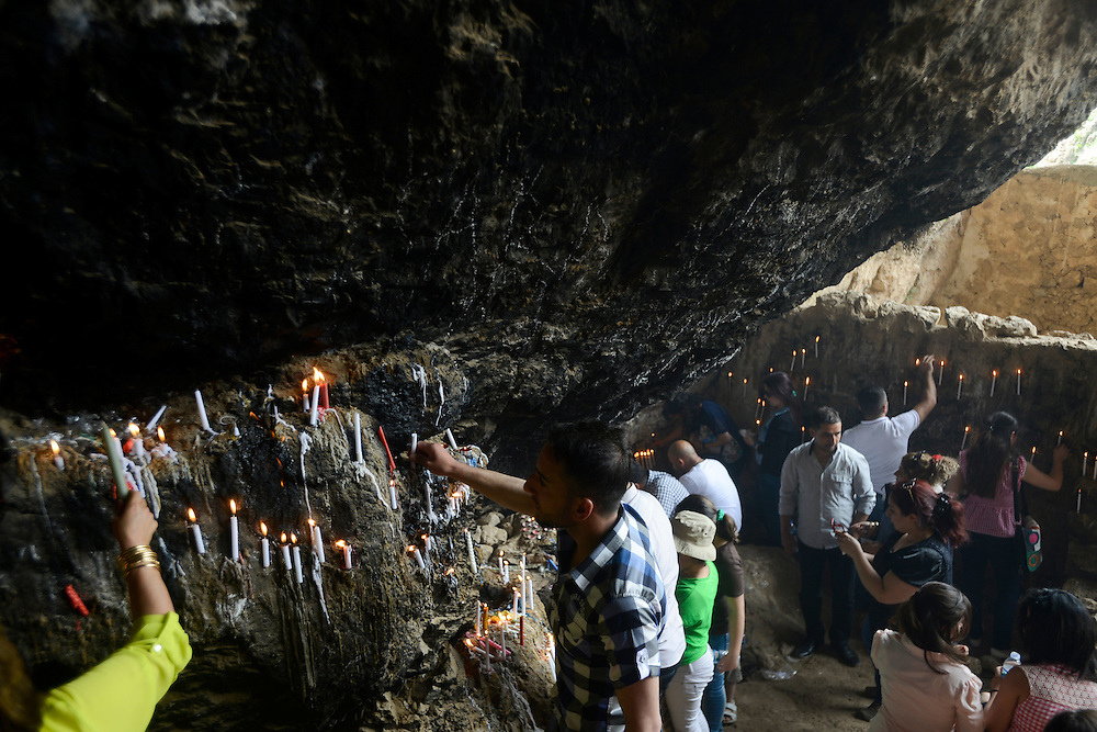 Christian pilgrims light candles inside the main cave at the Rabban Beya Temple. The 4th century Christian monastery is a series of monastic caves carved into a mountain high above the Shaqlawa valley and an important pilgrimage site for the Assyrian community. Shaqlawa, Iraq. 22/04/2014.
