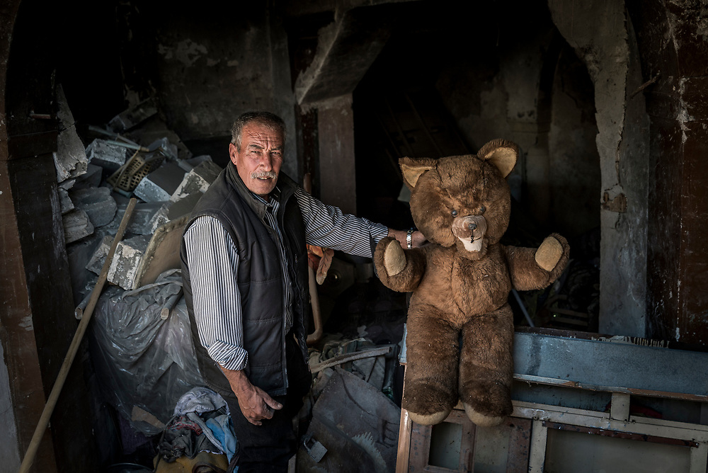A man holds a teddy bear found amongst the rubble of a destroyed house in the heart of Mosul's Old City.