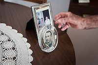 ACCIAROLI (POLLICA), ITALY - 5 OCTOBER 2016:  94-years-old Giuseppe Vassallo shows a picture of himself in his early 20's when he was an official of the Italian Navy, here in his house in Acciaroli, a hamlet in the municipality of Pollica, Italy, on October 5th 2016. Giuseppe Vassallo was an Italian Navy official during WWII. At age 86, 8 years ago, Mr Vassallo had multiple sex affairs to overcome his depression following his wife's death. He was a testimonial of the Acciaroli's mediterranean  diet and lifestyle during Expo 2015, the Universal Exposition hostel in Milan last year.<br /> <br /> To understand how people can live longer throughout the world, researchers at University of California, San Diego School of Medicine have teamed up with colleagues at University of Rome La Sapienza to study a group of 300 citizens, all over 100 years old, living in Acciaroli (Pollica), a remote Italian village nestled between the ocean and mountains in Cilento, southern Italy.<br /> <br /> About 1-in-60 of the area's inhabitants are older than 90, according to the researchers. Such a concentration rivals that of other so-called blue zones, like Sardinia and Okinawa, which have unusually large percentages of very old people. In the 2010 census, about 1-in-163 Americans were 90 or older.