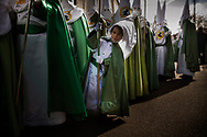 A penitent of the 'Virgen de la Esperanza' brotherhood looks from as he wait for the beginning of a Holy Week procession in Zamora, Spain, Thursday, April 2, 2015. Hundreds of processions take place throughout Spain during the Easter Holy Week.
