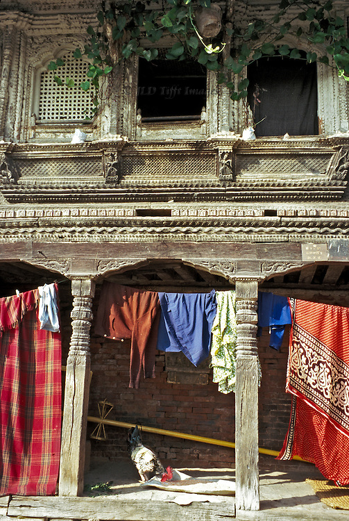 Old Newari carved wooden residence still occupied; laundry and bedding hang in its colonnade..