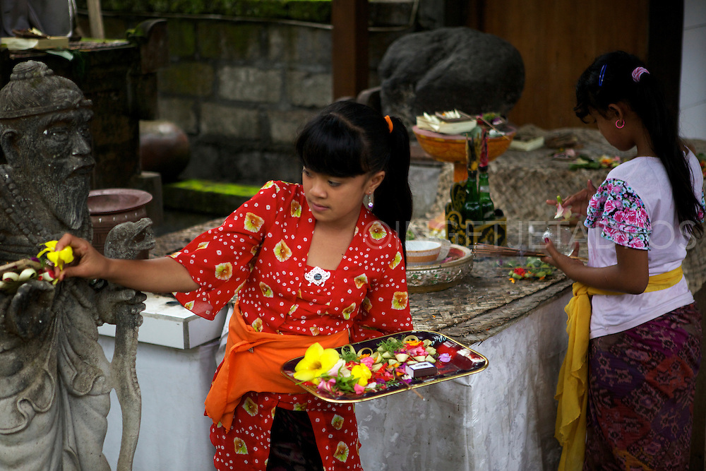 Two young Balinese girls performing a little ceremony in the early morning in Ubud. &copy;Ingetje Tadros<br />