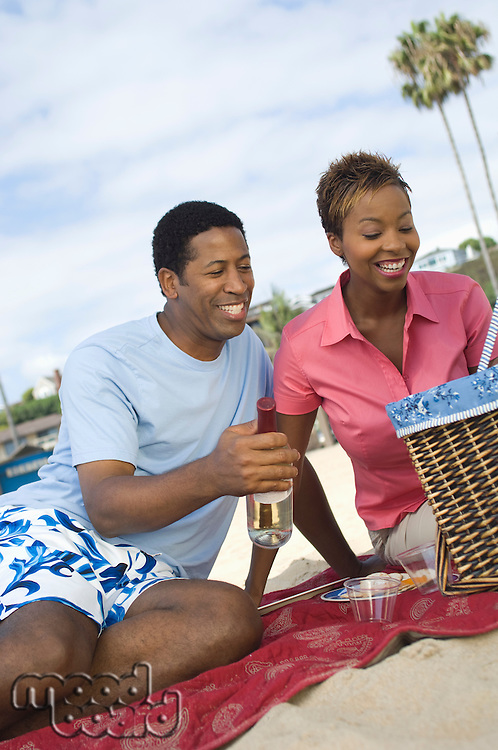 Middle-aged couple having picnic on beach