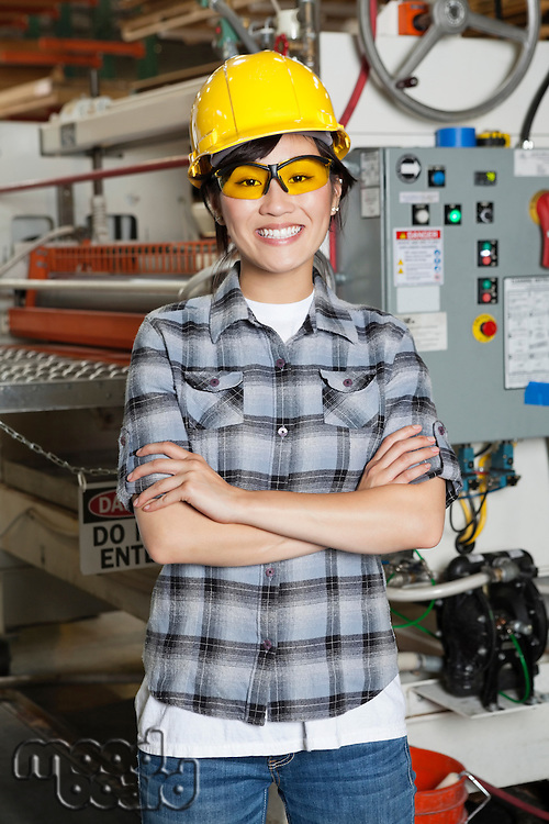 Portrait of happy Asian female industrial worker with machinery in background