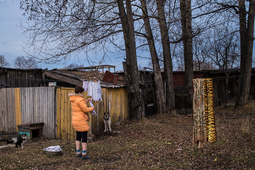 A woman hangs laundry outside her apartment on Wednesday, October 23, 2013 in Vydrino, Russia.