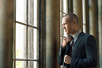 Businessman Adjusting Tie by window